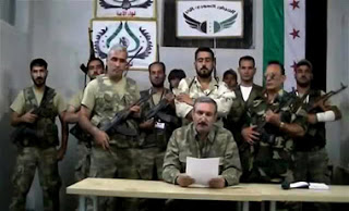 "An image grab taken from a video uploaded on YouTube on September 22, 2012 shows Free Syrian Army (FSA) chief Riad al-Asaad (C) reading a statement from an undisclosed location in Syria. Syrian rebels announced that their command centre has been transferred from neighbouring Turkey to inside Syria, in a video posted online. AFP PHOTO/YOUTUBE == RESTRICTED TO EDITORIAL USE - MANDATORY CREDIT ""AFP PHOTO/YOUTUBE"" - NO MARKETING NO ADVERTISING CAMPAIGNS - DISTRIBUTED AS A SERVICE TO CLIENTS - AFP IS USING PICTURES FROM ALTERNATIVE SOURCES AS IT WAS NOT AUTHORISED TO COVER THIS EVENT, THEREFORE IT IS NOT RESPONSIBLE FOR ANY DIGITAL ALTERATIONS TO THE PICTURE'S EDITORIAL CONTENT, DATE AND LOCATION WHICH CANNOT BE INDEPENDENTLY VERIFIED == SYRIA-CONFLICT-REBELS"